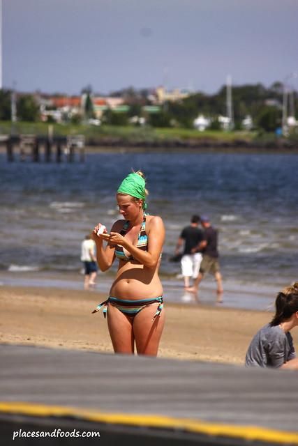 st kilda beach girl putting on tan