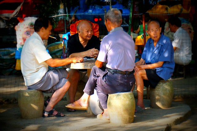Men playing cards at the park in Yangshuo.