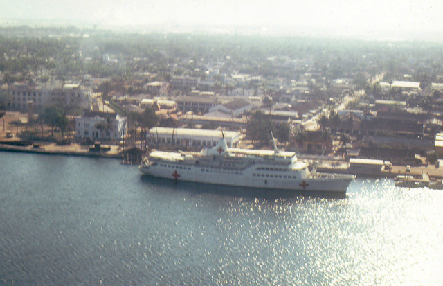 1968 Low aerial view of the Hospital ship Helgoland, a low aerial view of the Hospital ship Helgoland, docked on river in Da Nang, 1968