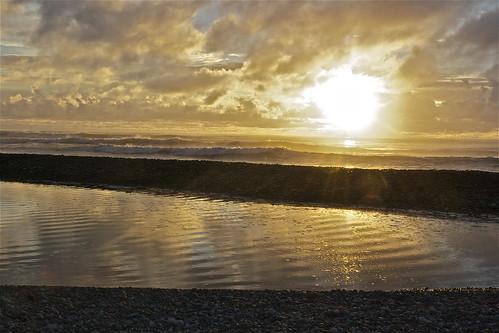 ocean light sunset sea newzealand cloud reflection beach water canon landscape gold coast stones shingle phormium ripples westcoast harakeke phormiumtenax rapahoe