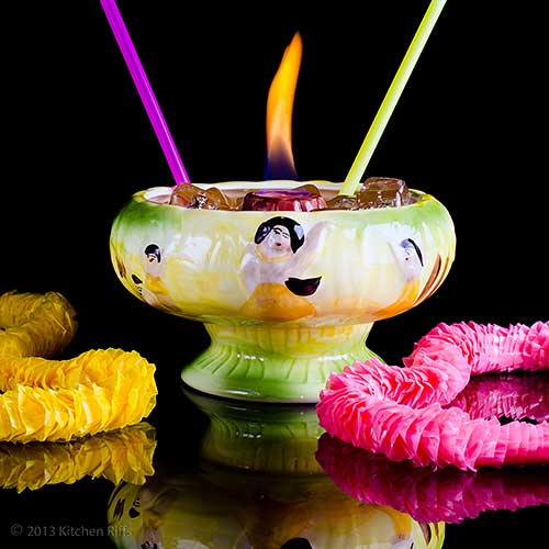 Volcano Bowl Cocktail in traditional Tiki volcano bowl with flaming crater, drinking straws, and flower leis