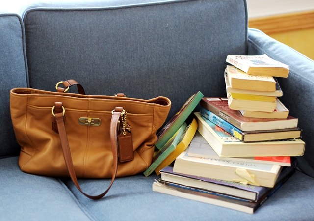 tan Coach purse and stack of books on blue coach