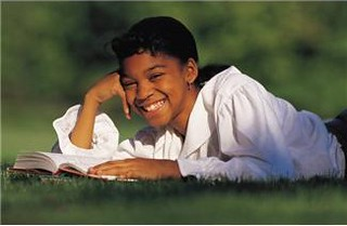 10 year old girl reading book in grass