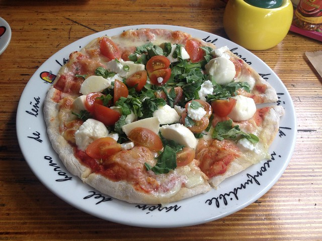 Pizza Marcopolo with mozzarella, goat cheese, tomatoes and arugula