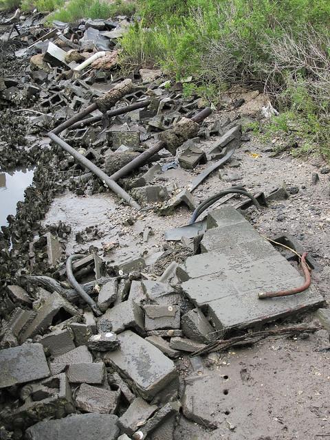 Mud-slickened riverbank cinderblocks.
