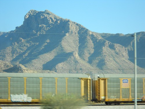 A possibly still train, blocked by a bush and telephone wires, with a faded mountain in the background.