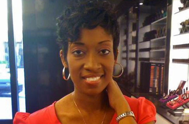 Marissa Alexander, a black woman with short hair wearing an orange shirt and hoop earrings.