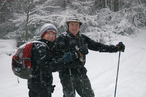 Two skiers enjoying the falling snow posing and for a photo op.