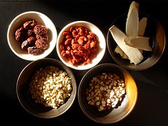 Five small bowls on a black background. Two of the bowls are white, and contain dried reddish fruits. The other bowls are black-and-brown; one contains long white strips and the others contain small white/brown seeds.