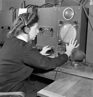 A member of the Women's Royal Canadian Naval Service (WRCNS) operating direction-finding equipment... / Une membre du Service féminin de la Marine royale du Canada faisant fonctionner de l'équipement de radiogoniométrie...