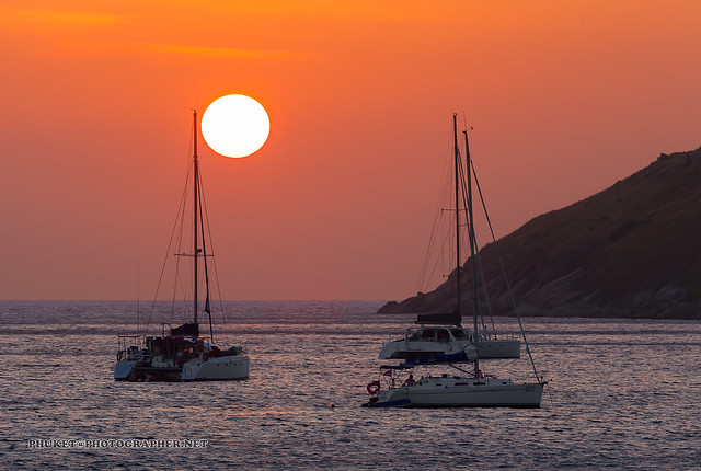 Sunset on the beacn with yachts and catamarans. Phuket
