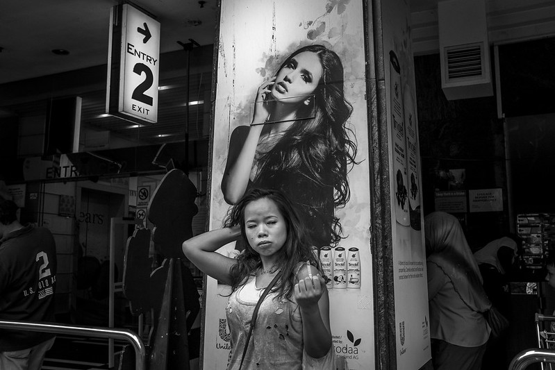 A woman with a cigarette in front of a poster.