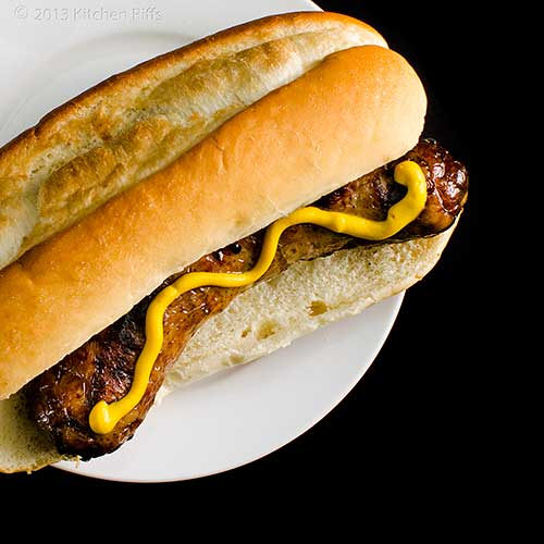 Grilled Bratwurst in bun with mustard, overhead view