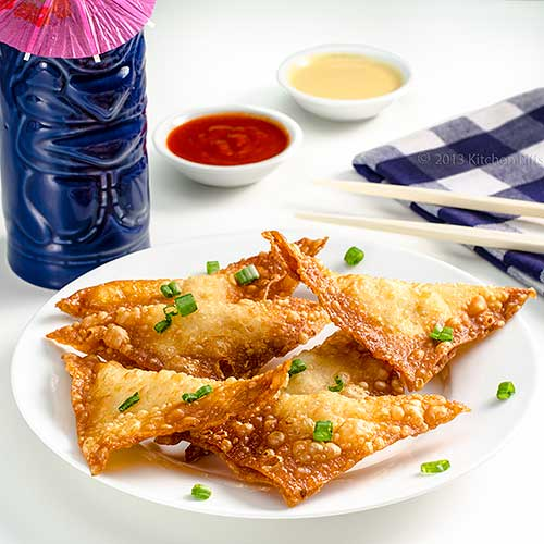 Crab Rangoon on plate with dipping sauces and Tiki Mug in background