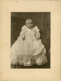 Baby in Long White Dress with a Hand at the Edge - Large Card Photogrph