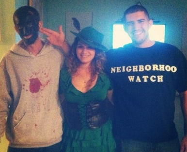 "A young white man in a ""neighborhood watch"" shirt holds his fingers like a gun to the head of a white boy in blackface"