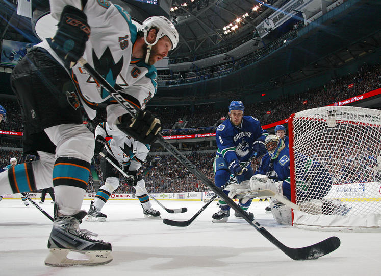 Sami Salo attempts to stop the Sharks' Joe Thornton.