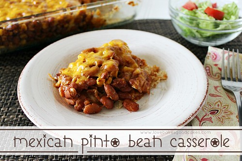 Mexican Pinto Bean Casserole on white plate with green salad and tomatoes