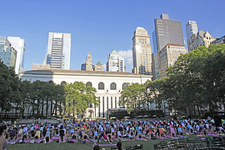 People Taken A Free Yoga Class In Bryant Park In New York City. Yoga Classes Are Taught Twice A Week By A Variety Of Talented Instructors. Thursday Evening Yoga Sessions Are On The Lawn. Yoga Mats Are Provided For Free. Photo Taken Thursday July 18, 2013