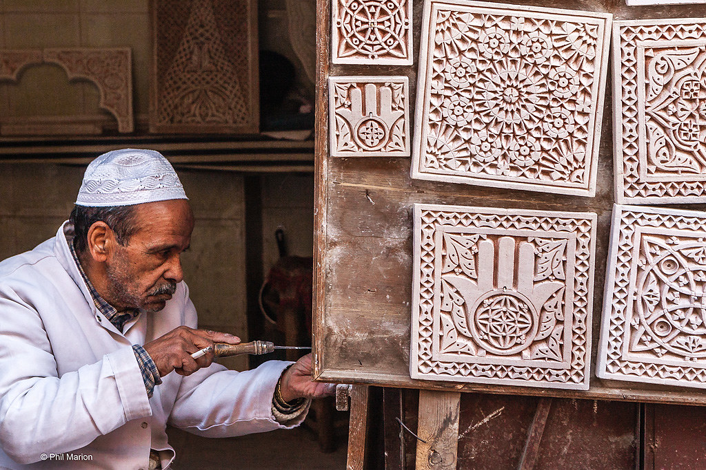 Craftsman making zellige - terra cotta tilework covered with enamel in the form of chips set into plaster