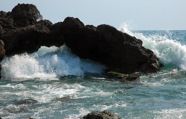 A wave joyfully fills the little arch, Pacific coast, Mazatlan, Mexico