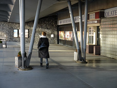 Woman walking along the waterfront IJ in the sun-light of December , in Amsterdam city; under the Piet Heinkade - a pedestrian route from city center to the Passengers Terminal on the border of river IJ; - urban photography by Fons Heijnsbroek, the Nether