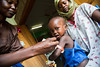 A nutrition specialist measures a child with severe malnutrition at the malnutrition ward in Al Shabbab hospital in Juba, South Sudan. He is using a Mid-Upper Arm Circumference (tape) which is a quick method of identifying which children are at risk of malnutrition and at which stage.  © Albert Gonzalez Farran, UNICEF