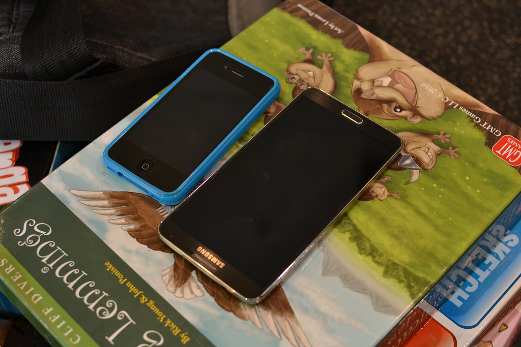 an iPhone 4S next to a large Samsung phone