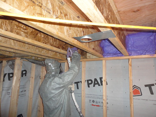 spraying the basement wall headers,