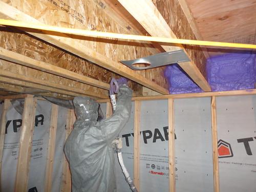 spraying the basement wall headers,