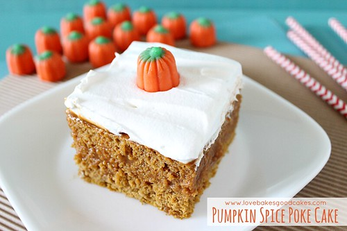 Pumpkin Spice Poke Cake piece with candy pumpkins on plate close up.