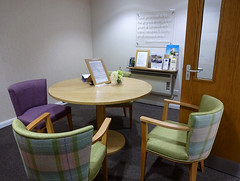 "A small room with light-coloured walls and a dark grey carpet.  Three chairs are arranged around a small round table in the centre; two upholstered in green and one in purple.  A transparent plaque on one wall reads: ""Our promise is to help you arrange or plan a funeral with care, respect, clarity and reassurance.  Croydon Funeralcare""."