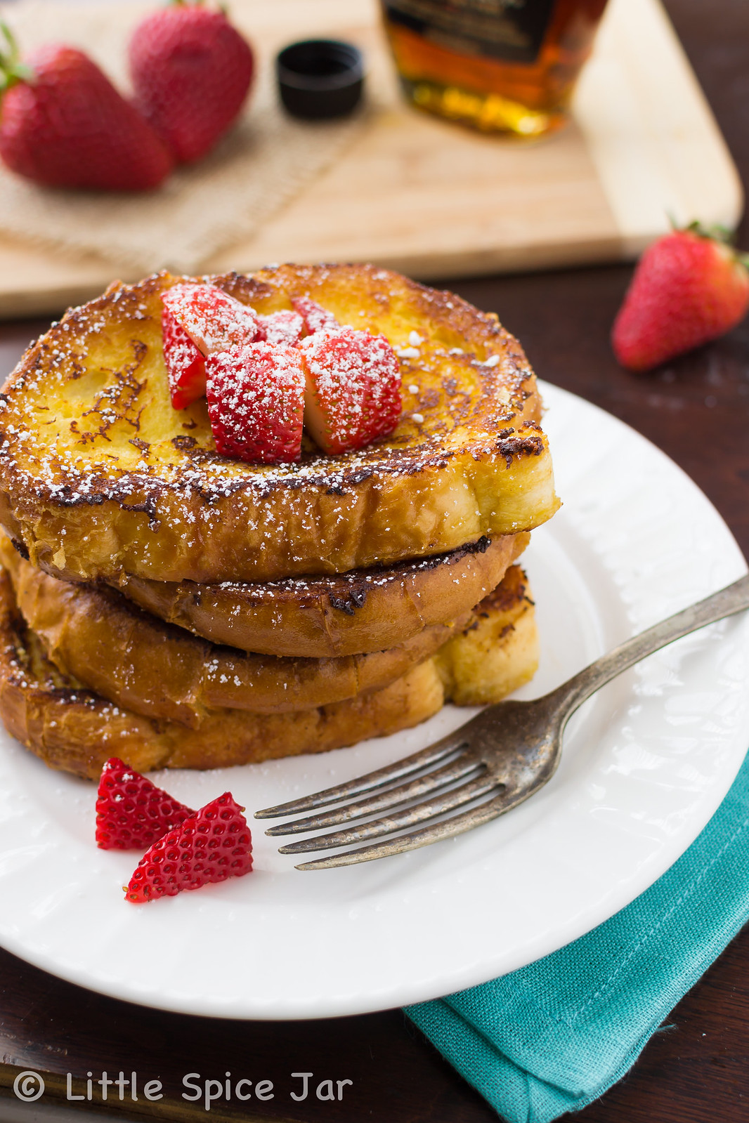 stack of French toast on white plate with fork and strawberries