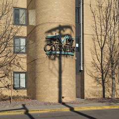 The elaborate Seven Corners Apartments logo is less impressive when it's getting messed with by a utility pole shadow at this time of year.