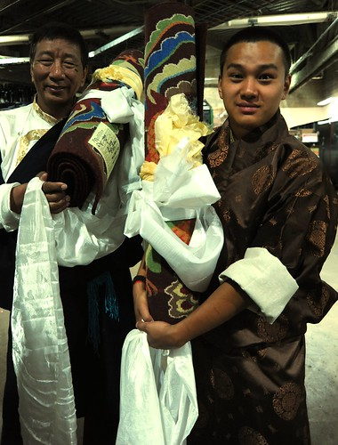 Two Tibetan men wearing traditional brown chubas with white shirts hold Tibetan carpets wrapped in khataks (ritual white scarves), an offering for His Holiness the Great 14th Dalai Lama, staging area, Kalachakra for World Peace, Verizon Center, Washington by Wonderlane