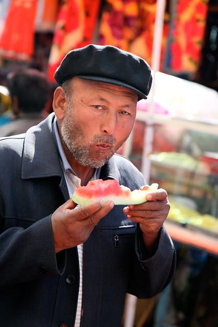 A man eating watermelon in the market, Urumqi ウルムチ、山西巷バザールで切り売りスイカを食べる男性