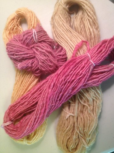 Four hanks of yarn, two dyed shades of pink and two shades of cream/beige.