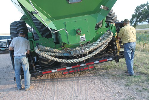 Dad and Brandon tightening the straps on the grain cart trailer.