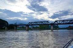 The infamous Bridge over the River Kwae at dusk seen from a long-tail boat, Kanchanaburi, Thailand