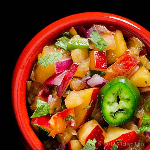 Plum Salsa with Jalapeño Garnish in red ramekin, overhead view on black