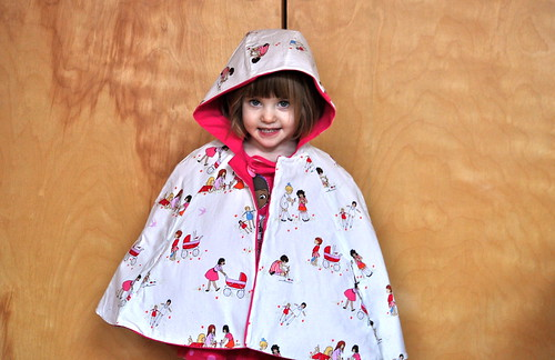 oliver + s red riding hood cape with children at play by sarah jane