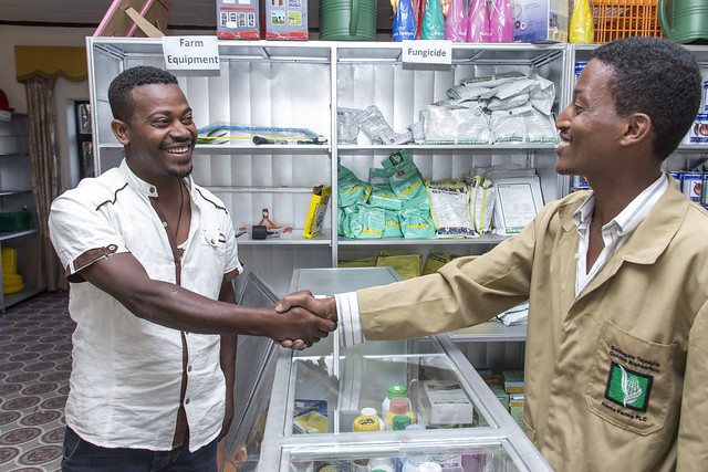A shop employee shakes hands with a customer