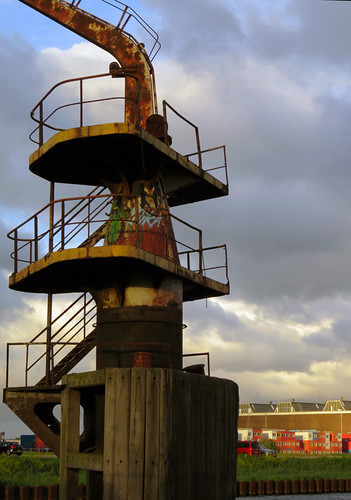 A spiral staircase leading up to a rusted crane in NDSM, an industrial area across the river from Amsterdam