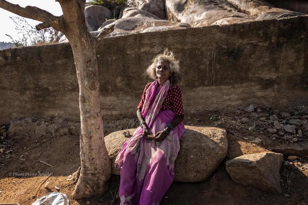 HAMPI : VIEILLE FEMME ASSISE SUR UN ROCHER