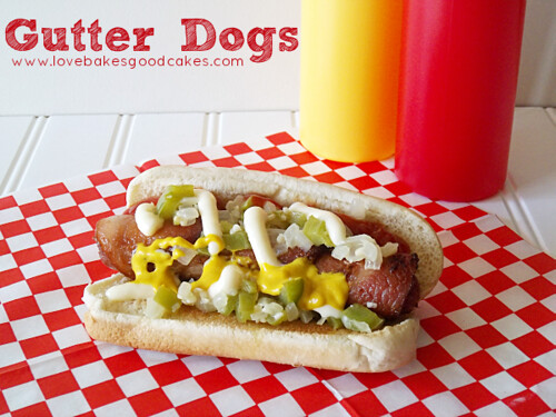 Gutter Dog on bun with ketchup, mustard, mayonnaise on checkerboard place mat.