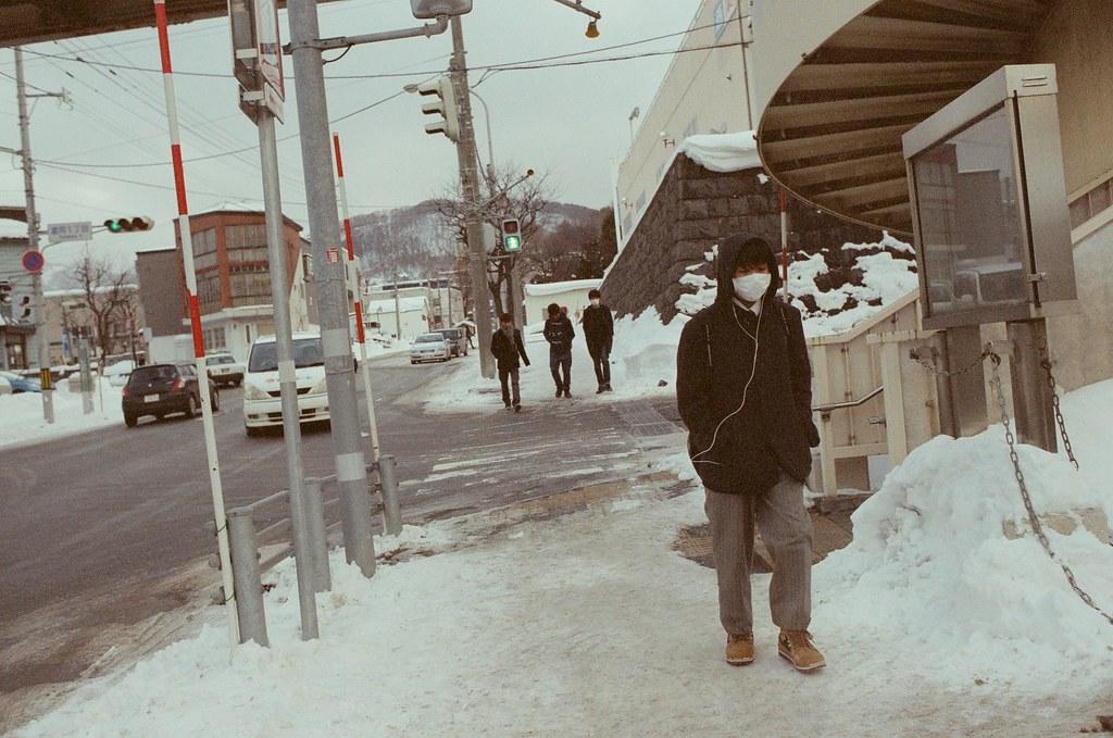 小樽 Otaru 北海道 / Fujifilm 500D 8592 / Nikon FM2 這也是繼續對著迎面而來的路人拍攝,那時候算是第一次來到有下雪的地方,不是很清楚在雪地生活的方式是什麼,所以看著當地人的穿著、步伐、應對方式都感到相當新奇。  剛好這兩張都帶著口罩,好像應該用這樣的方式防止臉凍傷齁!  Nikon FM2 Nikon AI AF Nikkor 35mm F/2D Fujifilm 500D 8592 1119-0026 2016/02/02 Photo by Toomore