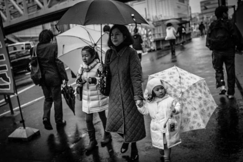 A mother leading her 2 daughters through the rain in Shinjuku, Tokyo