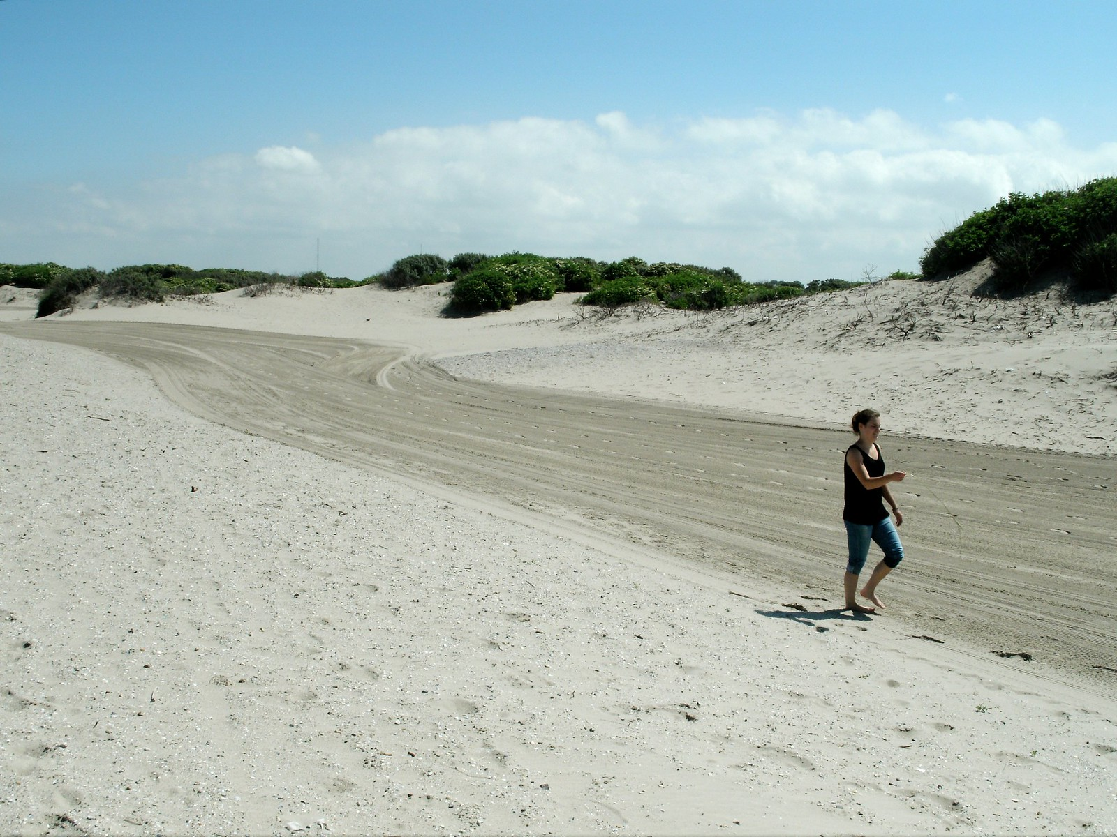A barefoot girl walks along a stretch of beach where vehicles have left their mark.