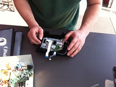 A set of hands working with a disassembled DVD player