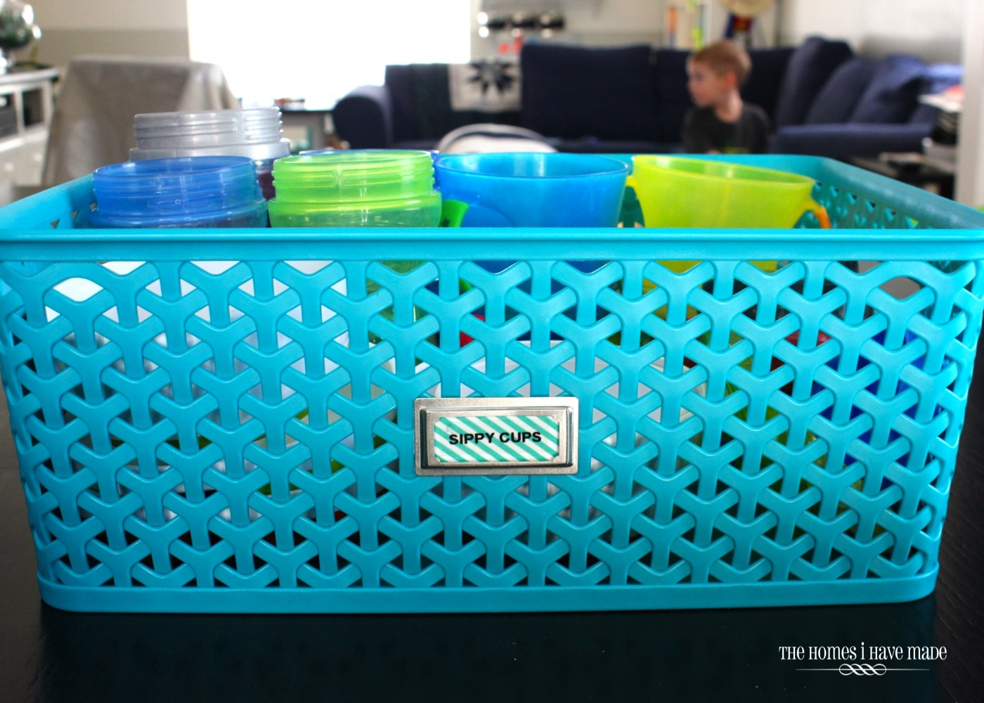blue basket containing blue and green sippy cups